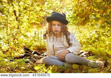 Portrait Of Young Funny Girl With Blonde Curly Hair And In Black Hat In An Autumn Park On A Yellow A