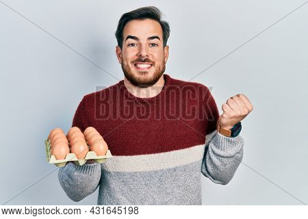 Handsome caucasian man with beard holding tray of fresh eggs screaming proud, celebrating victory and success very excited with raised arm