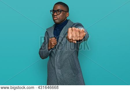 Young african american man wearing business clothes and glasses punching fist to fight, aggressive and angry attack, threat and violence
