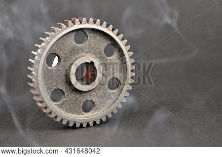 Engine Parts. Pinion On A Dark Background. Spare Parts.