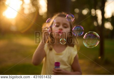 Focus On Soap Bubbles On The Blurred Background Of A Cute Baby Girl Blowing Soap Bubbles In Meadow,