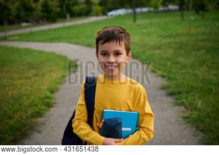 A Handsome Schoolboy With A Backpack And Notebooks Stands On The Path In The City Park After School.