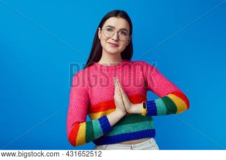 Attractive Cheerful Girl Keeps Palms Pressed Together In Praying Gesture, Wears Rainbow Sweater, Iso