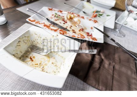 Empty Plates After A Meal In A Restaurant On The Table, Eaten Food In A Plate On A Wooden Table