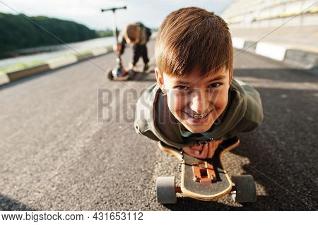 Boy With Braces Lying On A Skateboard, Close Up Portrait.
