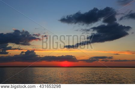 Dramatic sunset landscape with evening sky over lake water surface