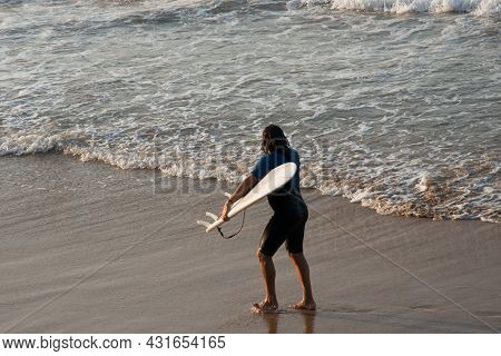 Surfer Coming Out Of The Sea With His Board. Gijon Beach, Asturias, Spain, Europe