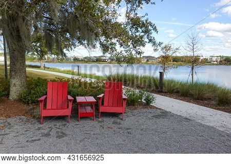 Two Chairs Sitting In A Park By A Lake In Laurete Park In Lake Nona, Orlando, Fl On A Beautiful Sunn