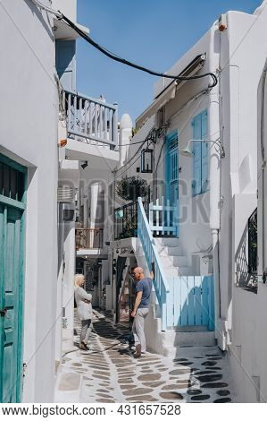 Mykonos Town, Greece - September 24, 2019: People Standing Talking By Whitewashed Buildings On A Nar