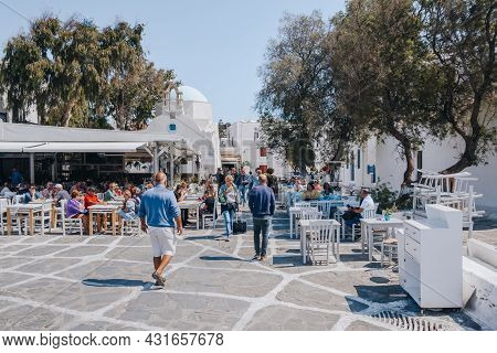 Mykonos Town, Greece - September 23, 2019: People Walking Past Restaurant Tables The On A Street In