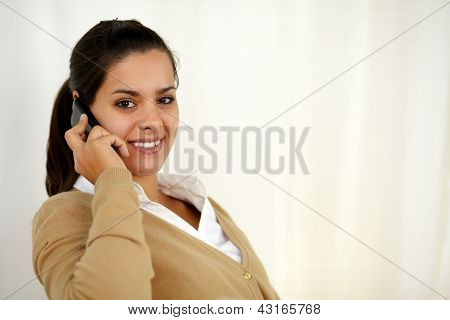 Smiling Latin Young Woman Speaking On Cellphone