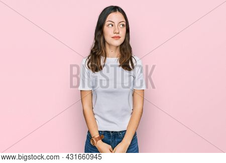 Young beautiful woman wearing casual white t shirt smiling looking to the side and staring away thinking.