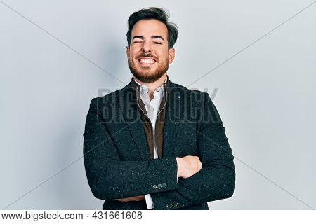 Handsome caucasian man with beard with arms crossed gesture winking looking at the camera with sexy expression, cheerful and happy face.