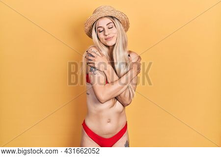 Young caucasian woman wearing bikini and summer hat hugging oneself happy and positive, smiling confident. self love and self care