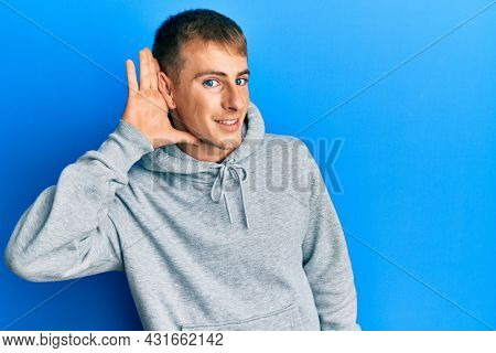 Young caucasian man wearing casual sweatshirt smiling with hand over ear listening and hearing to rumor or gossip. deafness concept.