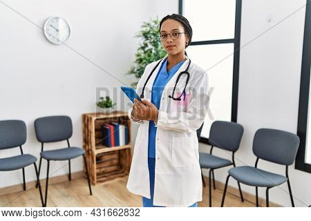 Young african american doctor woman at waiting room thinking attitude and sober expression looking self confident