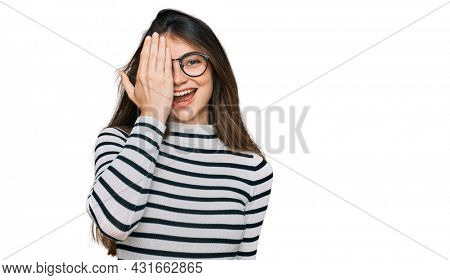 Young beautiful teen girl wearing casual clothes and glasses covering one eye with hand, confident smile on face and surprise emotion.