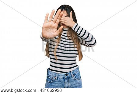 Young beautiful teen girl wearing casual clothes and glasses covering eyes with hands and doing stop gesture with sad and fear expression. embarrassed and negative concept.