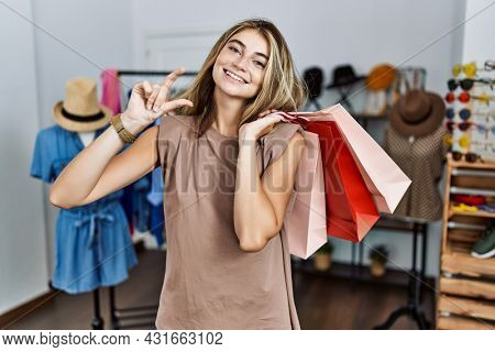 Young blonde woman holding shopping bags at retail shop smiling and confident gesturing with hand doing small size sign with fingers looking and the camera. measure concept.