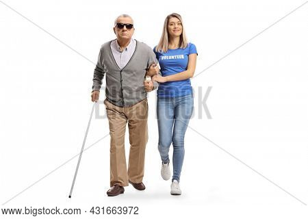 Full length portrait of a young female volunteer helping an elderly blind man walking with a cane isolated on white background