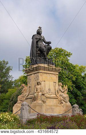 Amsterdam, Netherlands - August 14, 2021: Vondel Bronze Statue On His Beige Sculpted Pedestal Under