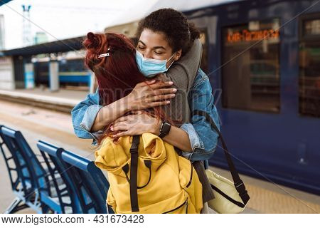 Multiracial two women in face mask hugging while saying goodbye at train station outdoors