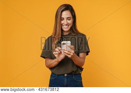 Happy mid aged casual woman using mobile phone while standing over orange background