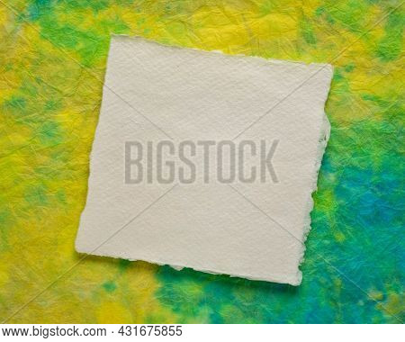 small sheet of blank white Khadi rag paper from South India against marbled handmade paper