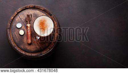 Lager beer mug and bottle opener on old wooden barrel. Top view flat lay with copy space