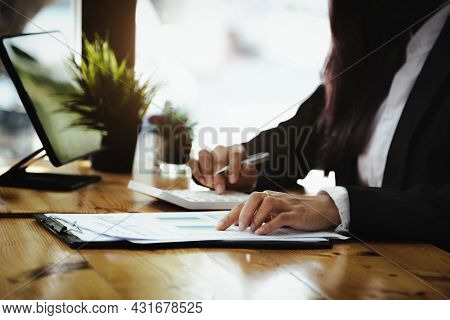 Business Woman Point To Document Budget And Using Calculator To Review Balance Sheet Annual To Calcu
