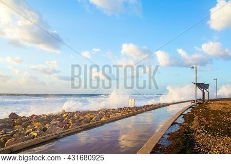 Embankment in Tel Aviv. Sunset. Powerful winter surf takes off with snow-white foam. Windy sunny day on the Mediterranean coast. Winter storm in the Mediterranean. Israel.