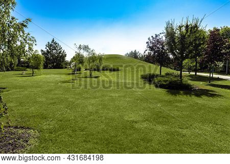 Summer Landscape With Green Lawn And Hill Surrounded By Trees