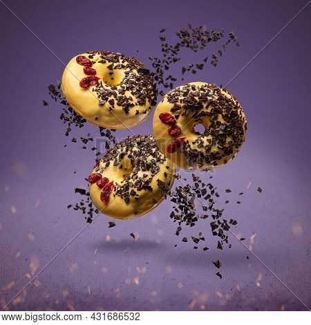 Flying Donuts. Doughnuts With Sprinkles On Purple Background