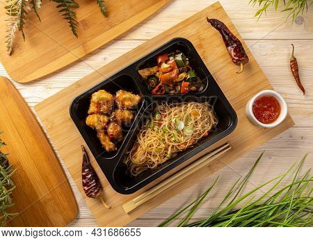 Flat Lay Of Noodles With Chicken Stew And Breaded Chicken Cubes In Take-out Box On Bamboo Chopping B