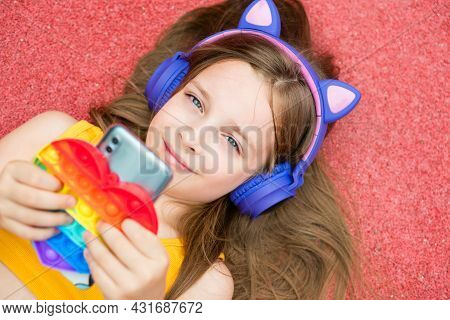 Pretty School Girl Hold Smartphone And Anti-stress Colorful Toy Pop It. Young Girl Chatting Friends,