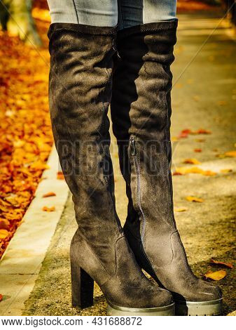 Woman Wearing Long Black Heeled Knee High Boots And Jeans. Autumn Fashion, Warm Footwear Boots.