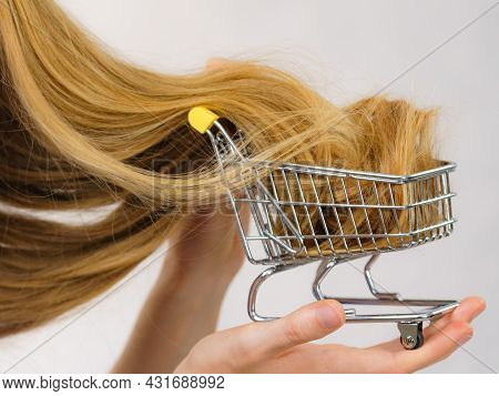 Girl With Her Long Straight Blonde Hair In Shopping Cart For Selling. Haircut Haircare And Shopping