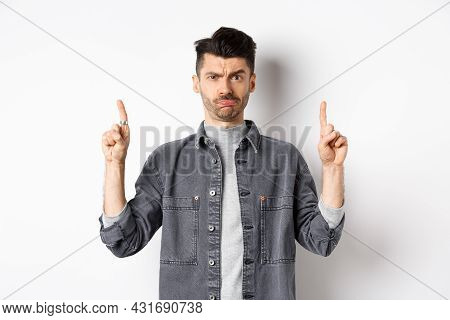 Confused Funny Guy With Moustache Pointing Fingers Up At Something Strange, Frowning And Pouting Puz