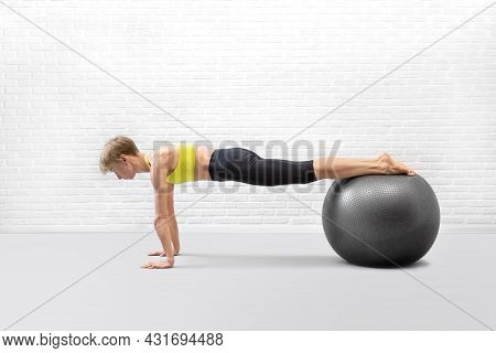 Workout With Props. Slim Attractive Caucasian Woman Does Plank Balance Drill Using Fitness Ball In L