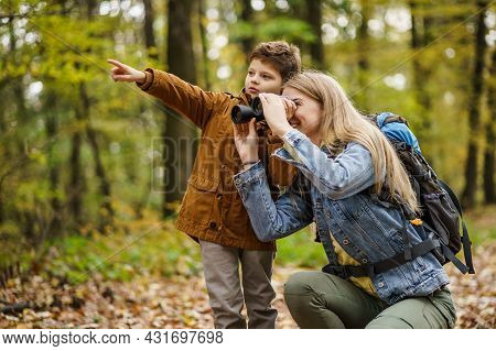 Happy Mother And Son Are Hiking In Forest. They Are Watching Nature With Binoculars.