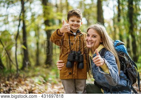 Happy Mother And Son Are Hiking In Forest In Autumn.