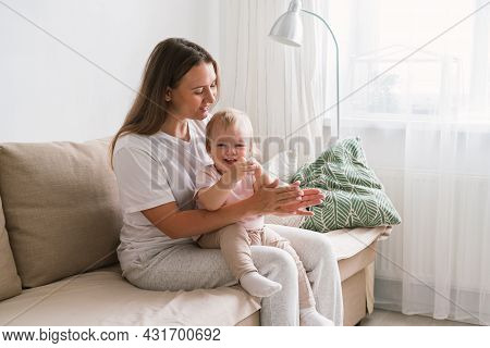 Horizontal Of Mum Clapping And Looking At Blond Child Sitting On Couch In Living Room. Mommy Spendin