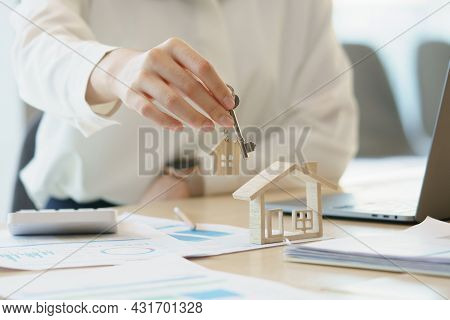 Woman Holding Keys House With House Shaped Keychain And Home Mockup On Wooden Table.real Estate Conc
