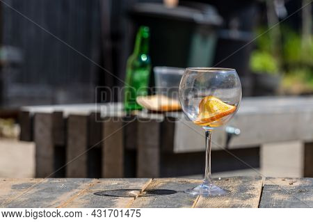 Empty Wine Glass On Wooden Table, Background Blurred Empty Green Bottle And Plastic Cup On Rustic Ta