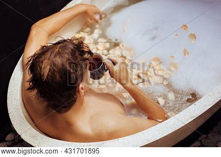 Man Lying In Bath Tub With Soap Foam, Petals, Mug