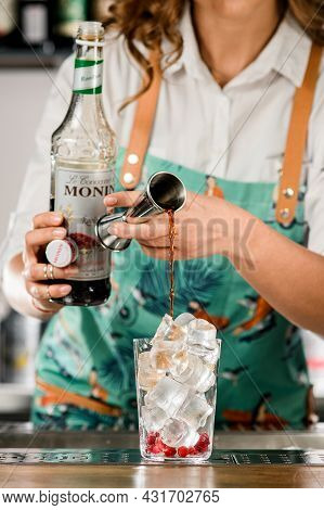 Ukraine, Kyiv - March 12, 2021: Female Bartender Holds Jigger And Pours Drink Into Glass With Ice Cu