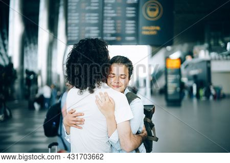 Young Family Couple At The Airport Departure Area Saying Goodbye Or Hello, Embracing Each Other With