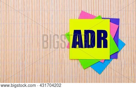 On A Light Wooden Background, Bright Multicolored Stickers With The Text Adr Alternative Dispute Res