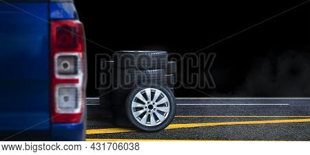Wheel And Tire Pile On The Asphalt Road With Black Background At Night