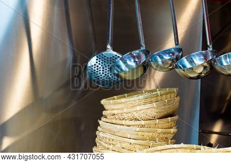 Kitchen Utensils In The Restaurant Kitchen. Soup Ladles Hang Over Wicker Plates. Kitchen Tools For P